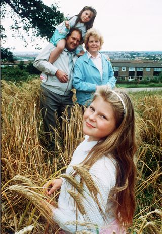 Tight Knit: Louise (in white), ahead of her tenth birthday, with her parents—John and Lesley—and younger sister Natalie | Getty Images