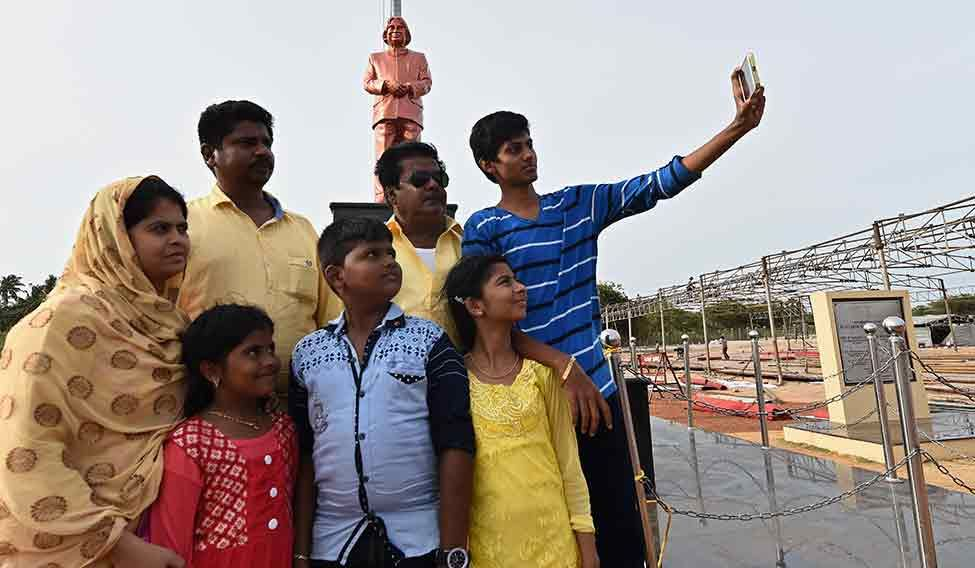 A family takes a selfie with Kalam's statue