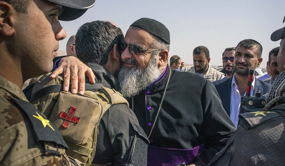 In good faith: A bishop greets an Iraqi soldier near the Bartella front line.
