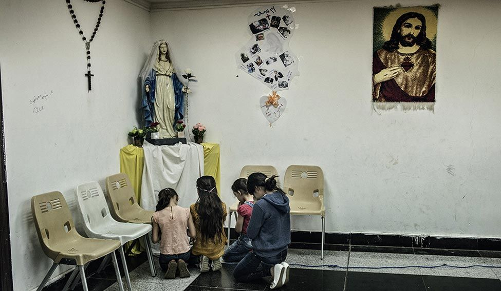 Hope springs eternal: Girls pray at a makeshift prayer room at a shopping mall in Erbil.