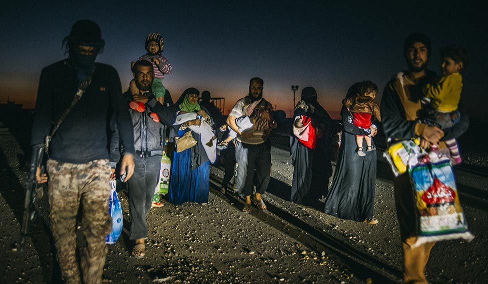 All is not lost: Families fleeing Mosul at night.