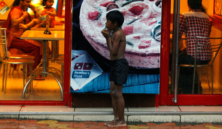 Unequal hunger: a homeless boy takes shelter from rain outside a fast food shop in Mumbai | Reuters