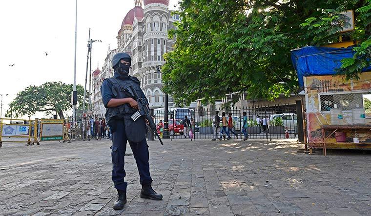 On guard: A Force One commando outside the Taj hotel.