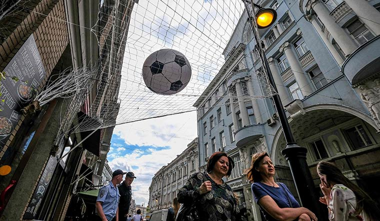High hopes: People walk past a cafe decorated with an overhead football-themed installation in Moscow | AFP