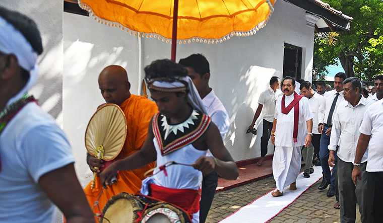 Lanka's white knight?: Rajapaksa on his way to take part in the poya ceremony at the Buddha temple behind his residence.