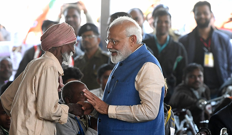 Reaching out: Modi in conversation with a  physically challenged person at Audhe village.