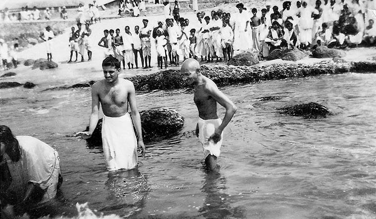 Cleansing ritual: Gandhi taking a bath at Kanyakumari, Tamil Nadu, in 1934 | Dinodia