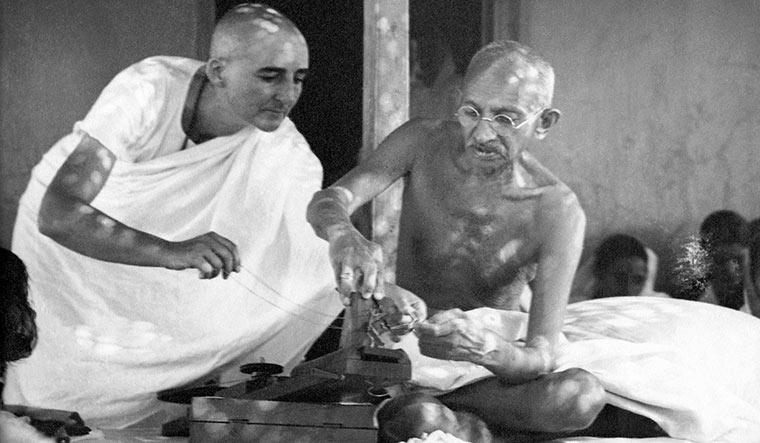 Ashram life: Gandhi repairing his charkha, assisted by his British co-worker Madeleine Slade, whom he named Mirabehn, at Sevagram Ashram | Dinodia