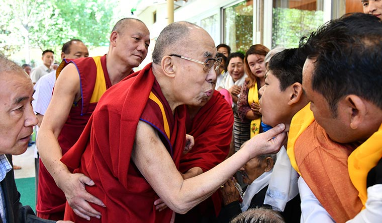 Holy encounter: The Dalai Lama blesses a child outside his residence in Mcleodganj.