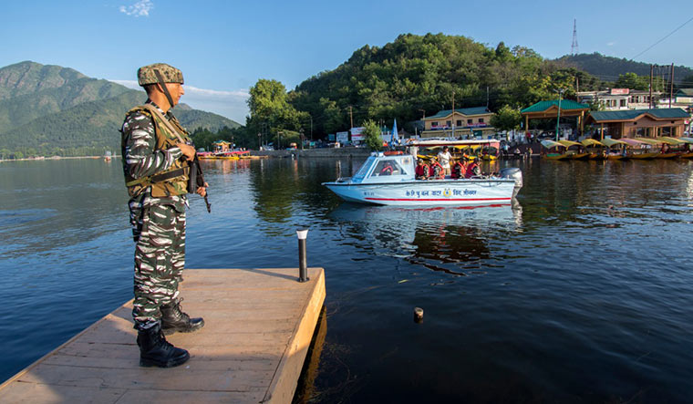 Watchful eyes: A soldier standing guard at Dal Lake in Srinagar.