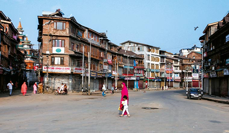 Silent valley: A few residents walk the streets of Srinagar amid restrictions | Reuters