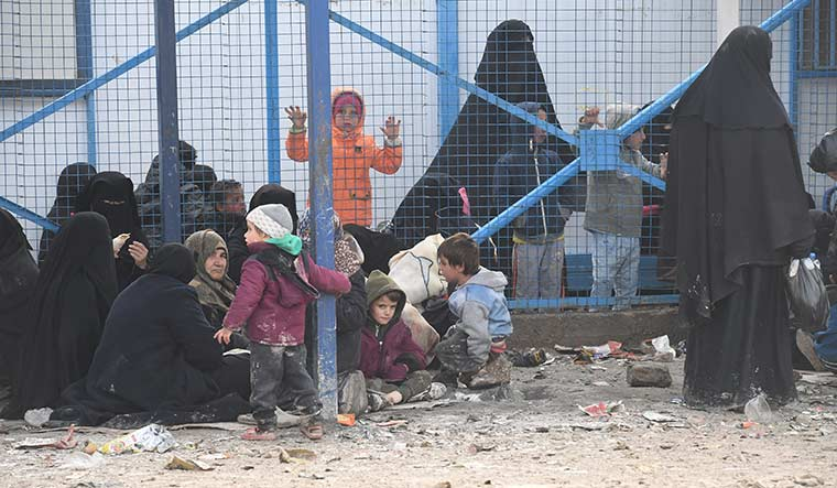 Lives in limbo: Women and children waiting outside a medical centre in the Al-Hol camp.