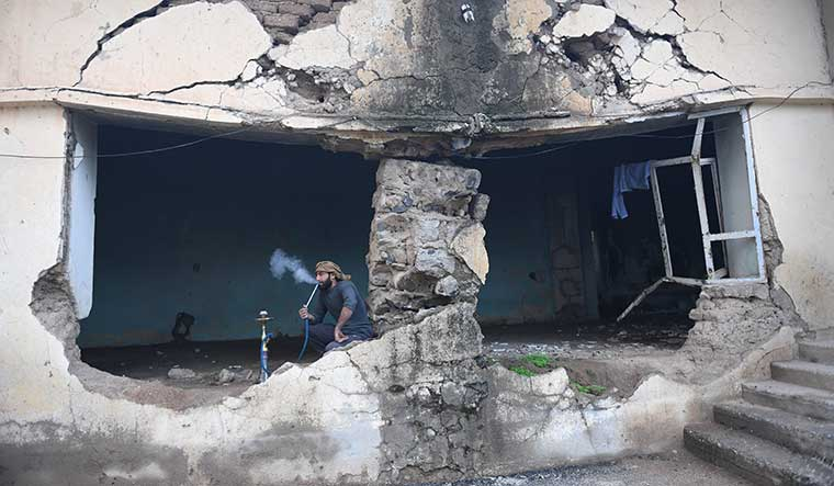 Testing times: The caretaker of the Sheikh Al Haz Navi mosque in northeastern Syria's Jal Maruf village enjoys a smoke. The mosque was destroyed by Islamic State terrorists.
