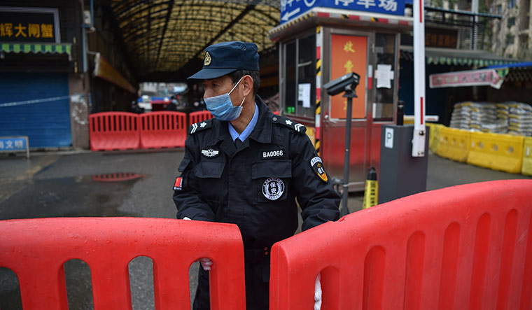 On the qui vive: A police officer stands guard outside the Huanan Seafood Market | AFP
