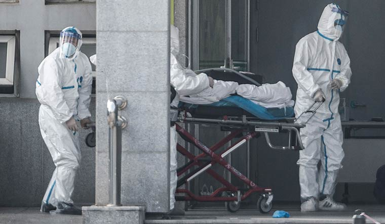 Grim picture: Medical staff carrying a patient with coronavirus symptoms at the Wuhan Jinyintan Hospital | AFP