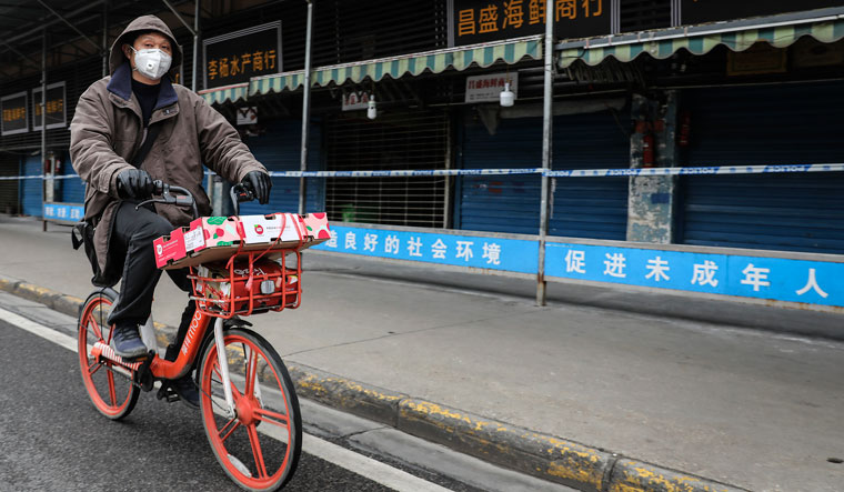 Shutters down: A photo taken in January shows a man ride past the closed Huanan Seafood Wholesale Market, which has been linked to initial Covid  19 cases, in Wuhan, China | Getty Images