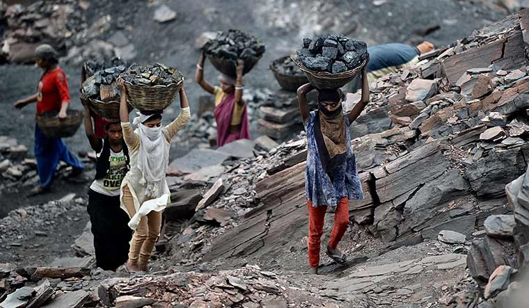 Heavy load: Women and children carry coal in baskets.