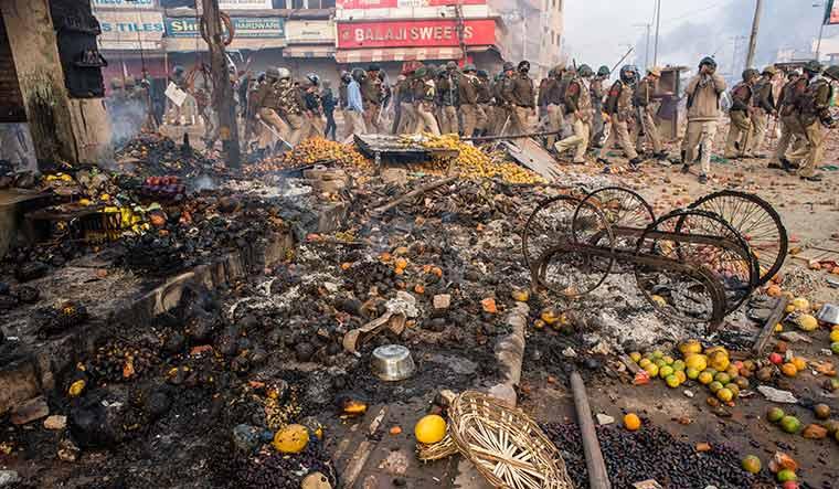 Passive force: Policemen walk past shops set ablaze during the Delhi riots | Getty Images