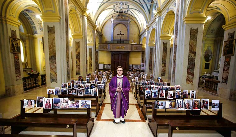 In God, we trust: Don Giuseppe Corbari, parson of the Robbiano church in Giussano, northern Italy, poses next to selfies sent by his parishioners after services were suspended following the coronavirus emergency | AP