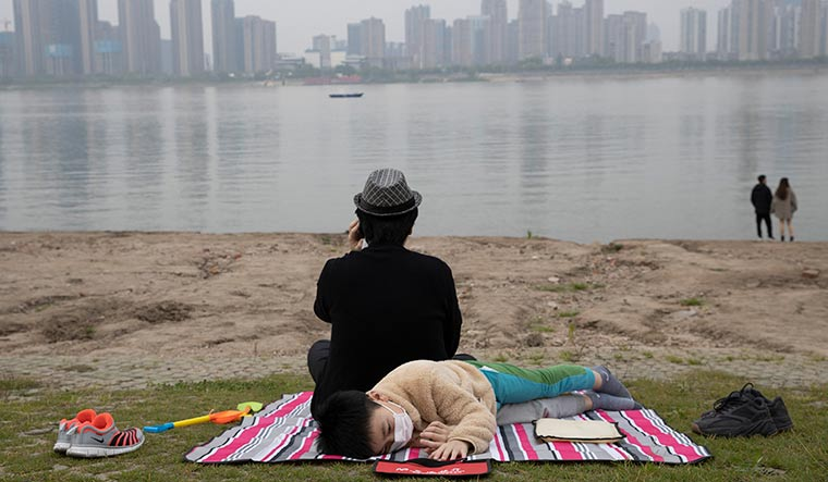 Ground zero: A child resting on the banks of the Yangtze in Wuhan. The epicentre of Covid-19, Wuhan is limping back to normal | AP