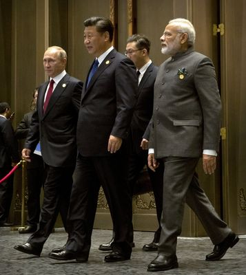 Power games: Russia's President Vladimir Putin with Xi Jinping and Prime Minister Narendra Modi in Xiamen, southeast China, in 2017. Russian intervention could hold the chinese army back with no further bloodshed | Reuters