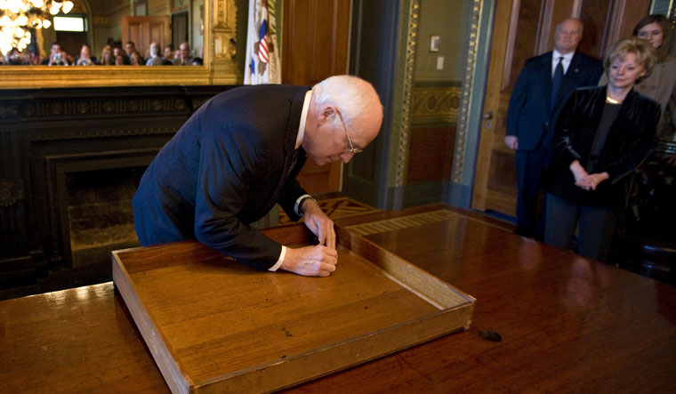 The forever mark: In a time-honoured tradition, Cheney signs the top drawer of the desk in the vice president's ceremonial office | Getty Images