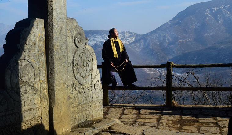 My lord, my Damo: Shi Yanyuan, a monk, in a pensive mood near the  Bodhidharma cave in the Wuru Peak. Behind him is the Shaoshi mountain, from which came the name Shaolin