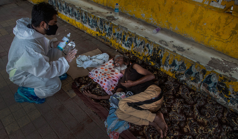 Coax, vax: A health worker persuades a homeless man to get himself inoculated against Covid-19 in Guwahati | AP