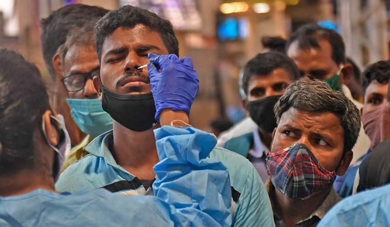 Late vigil: Health workers collect nasal swabs from passengers at Chhatrapati Shivaji Maharaj Terminus in Mumbai | Amey Mansabdar