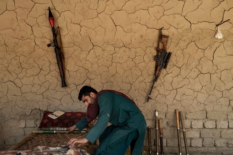 Ready to retaliate: A member of the Bati Kot militia arranging rocket-propelled grenades at a checkpoint.