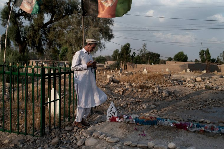 Gone, but not forgotten: A man offers prayers near the grave of his slain daughter in Jalalabad .