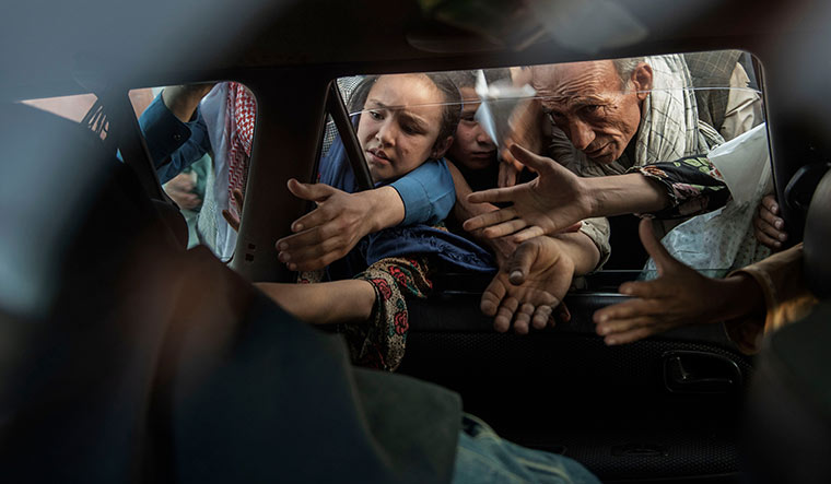 Hungry, hopeless: People begging for food from travellers in Kabul. The city's population nearly doubled because of the influx of refugees in the final days of the war.