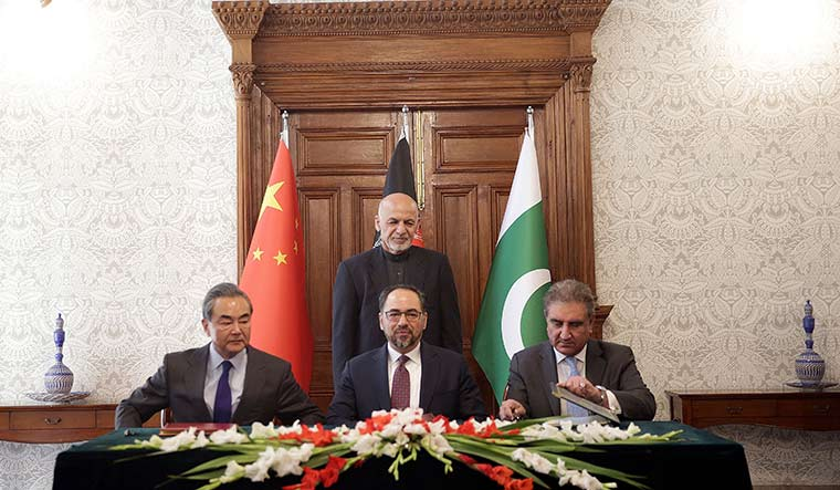 Three to tango: Former Afghanistan president Ashraf Ghani (standing) with (from left) Chinese Foreign Minister Wangi Yi, former Afghanistan foreign minister Salahuddin Rabbani, and Pak Foreign Minister Shah Mehmood Qureshi at the trilateral meet in Kabul in 2018 | AP