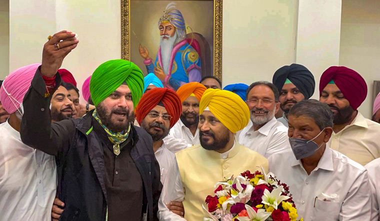 New innings: (From left) Punjab Congress president Navjot Singh Sidhu with Chief Minister Charanjit Singh Channi and Congress general secretary Harish Rawat after Channi's oath-taking ceremony in Chandigarh   PTI