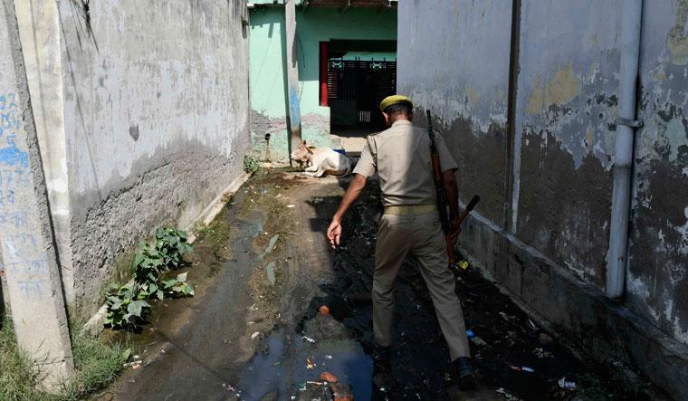 Keeping watch: A policeman patrols a lane near the victim's house |  Sanjay Ahlawat