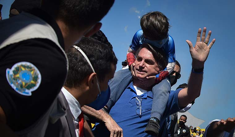 Ignorance at play: President Jair Bolsonaro carries a boy on his back as he greets supporters gathered outside the presidential palace in Brasilia | AP