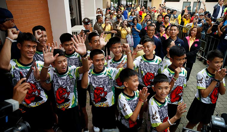 Welcome, wild boars: People cheer for coach Ek (far left) and the12 boys as they arrive for the press conference | Reuters