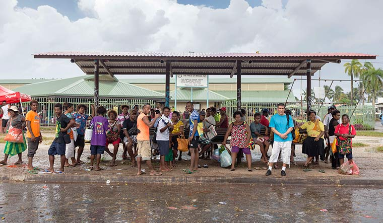 Blending in: An Afghani asylum-seeker (in blue T-shirt) at a bus shelter in Manus Island | Getty Images