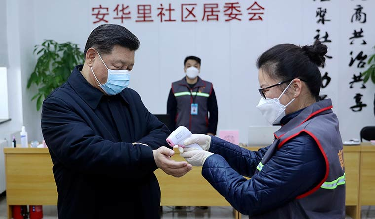 By the rules: President Xi Jinping gets his temperature checked during a visit to a community health centre in Beijing | AP