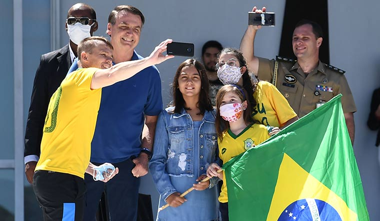 Fan base: Brazilian President Jair Bolsonaro and his daughter Laura pose for a selfie with supporters outside Planalto Palace in Brasilia | AFP