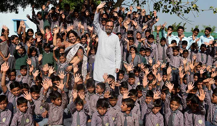 Dedicated duo: Nilesh Desai and his wife, Prakshali, with the children of Buniyadi Shala.