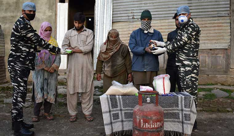 Helping out: CRPF personnel provide essentials to residents of Humhama, Budgam district, Jammu and Kashmir.