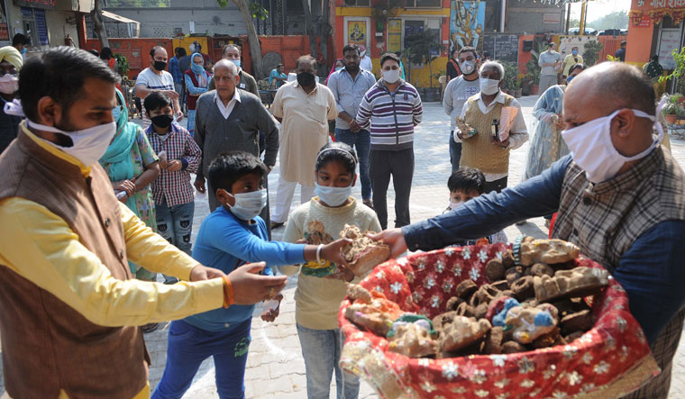 Going green: Members of Gouri Shankar Sewa Dal in Chandigarh distributing diyas and idols made of cow dung ahead of Diwali in November last year | Getty Images