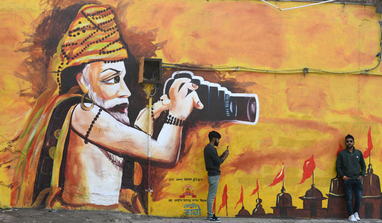 People pose for photograph against the backdrop of a brightly painted graffiti wall