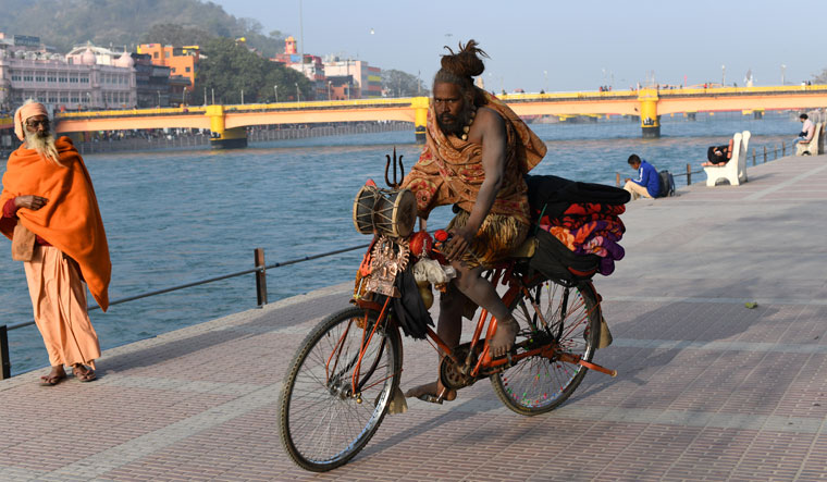 A sadhu carries a few belongings with him on his cycle