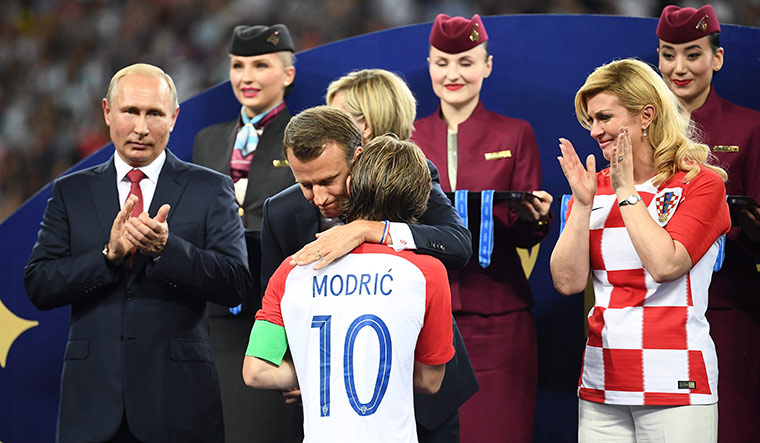 Global fraternity: French President Emmanuel Macron hugs Croatia's Luka Modric as Russian President Vladimir Putin (left) and Croatian President Kolinda Grabar-Kitarovic look on | AFP