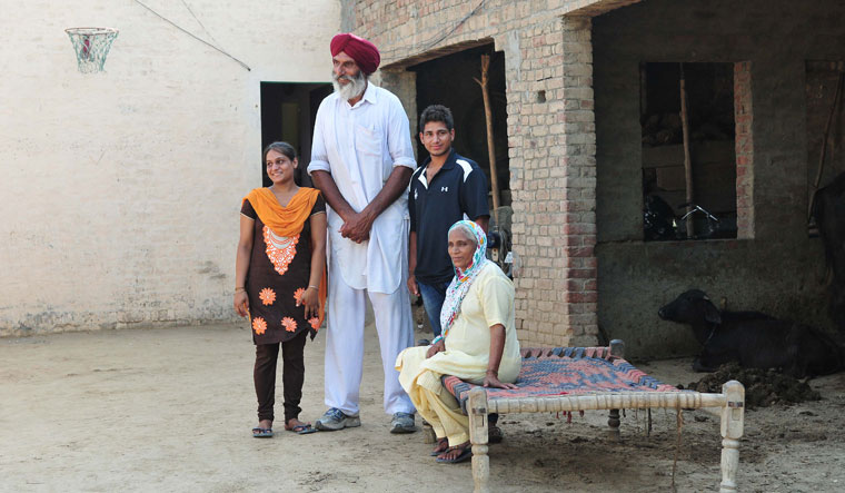 Family to the fore: Satnam's father, Balbir Singh Bhamara, with wife and two children. His father's income from farming supports the family now | Getty Images