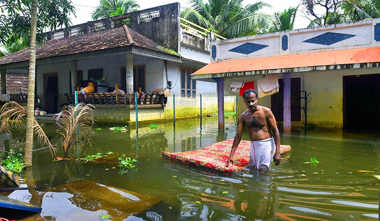 Bed of sorrow: Appukkuttan of Kainakiri in Alappuzha takes out the bed he had bought for his daughter just before the floods | Sanjoy Ghosh