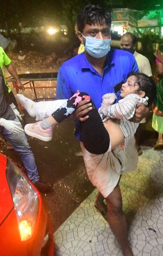 Rush to rescue: A child injured in the air mishap at the Kozhikode airport being taken to a hospital | Hashim P.K.