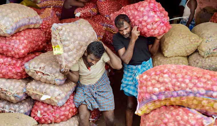 Onion-workers-carrying-sacks-PTI